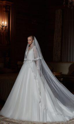 Закрытое свадебное платье с длинными кружевными рукавами и роскошной многослойной юбкой.