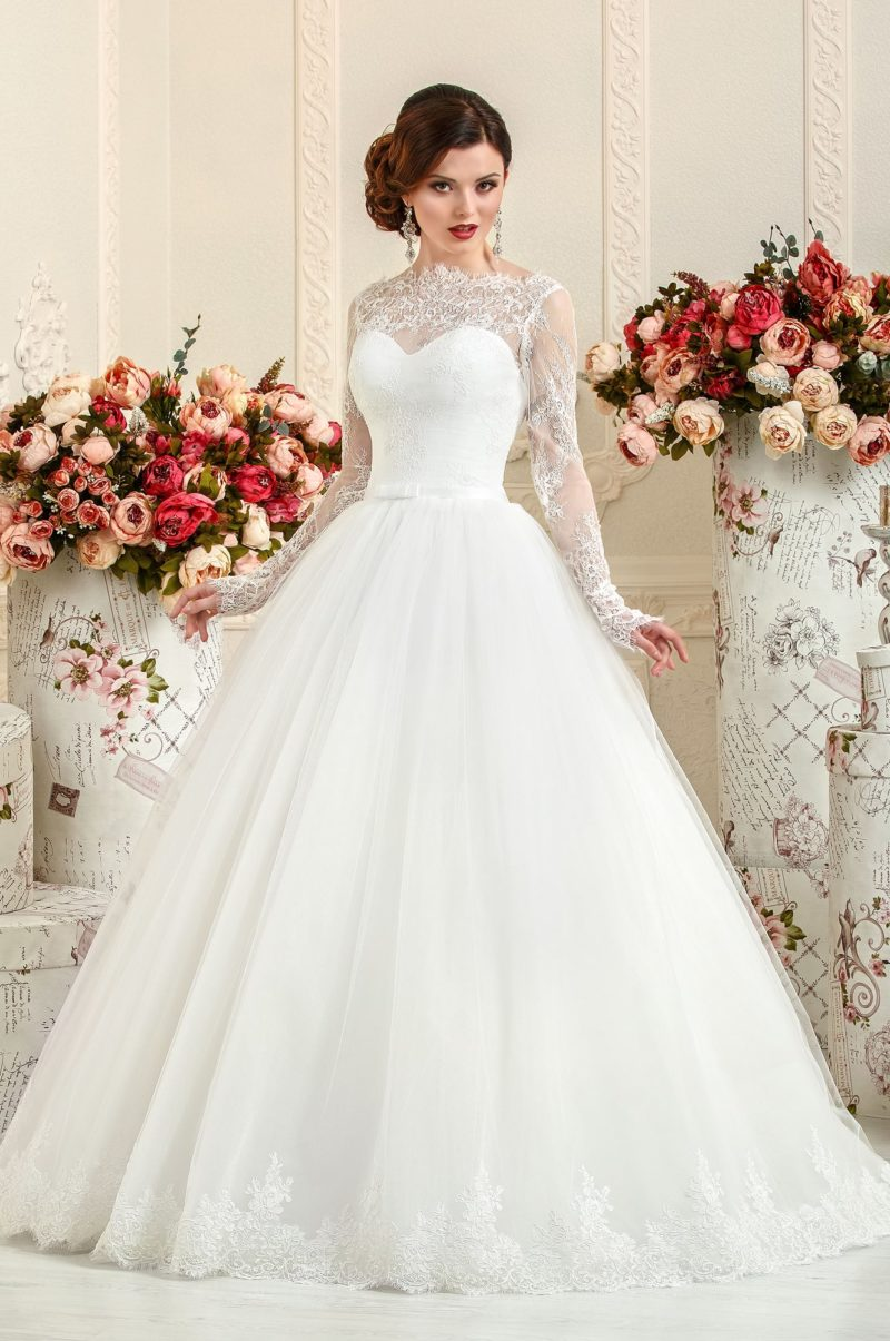 Скромное свадебное платье с роскошной многослойной юбкой и высоким вырезом.