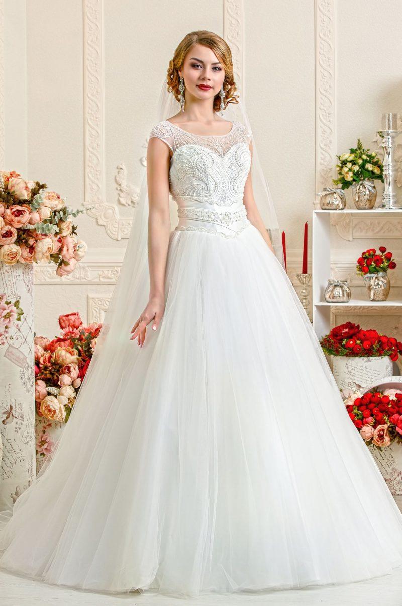Закрытое свадебное платье А-силуэта с полупрозрачной тканью отделки верха, украшенной бисером.