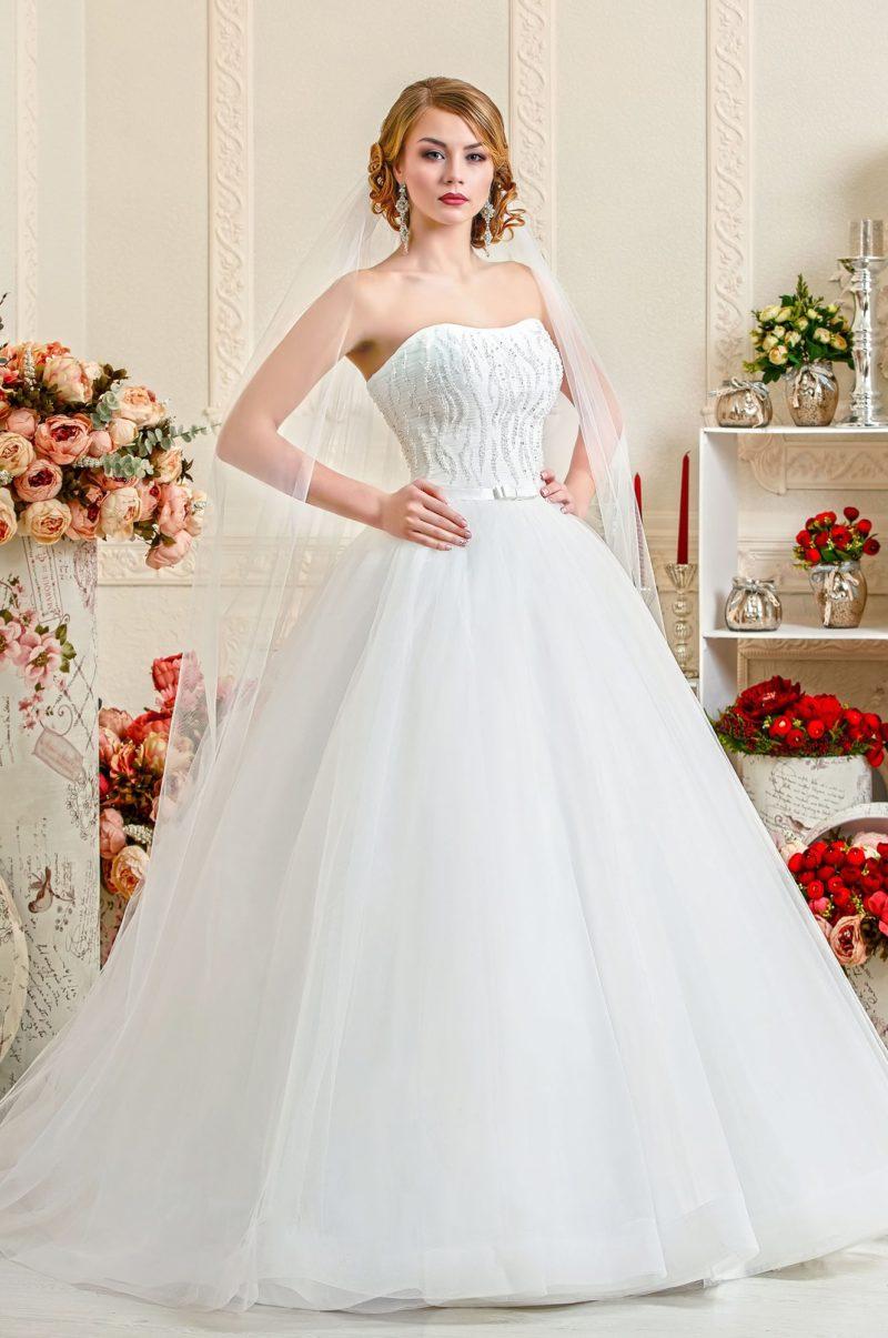 Впечатляющее свадебное платье с объемной юбкой и открытым корсетом, покрытым вышивкой.