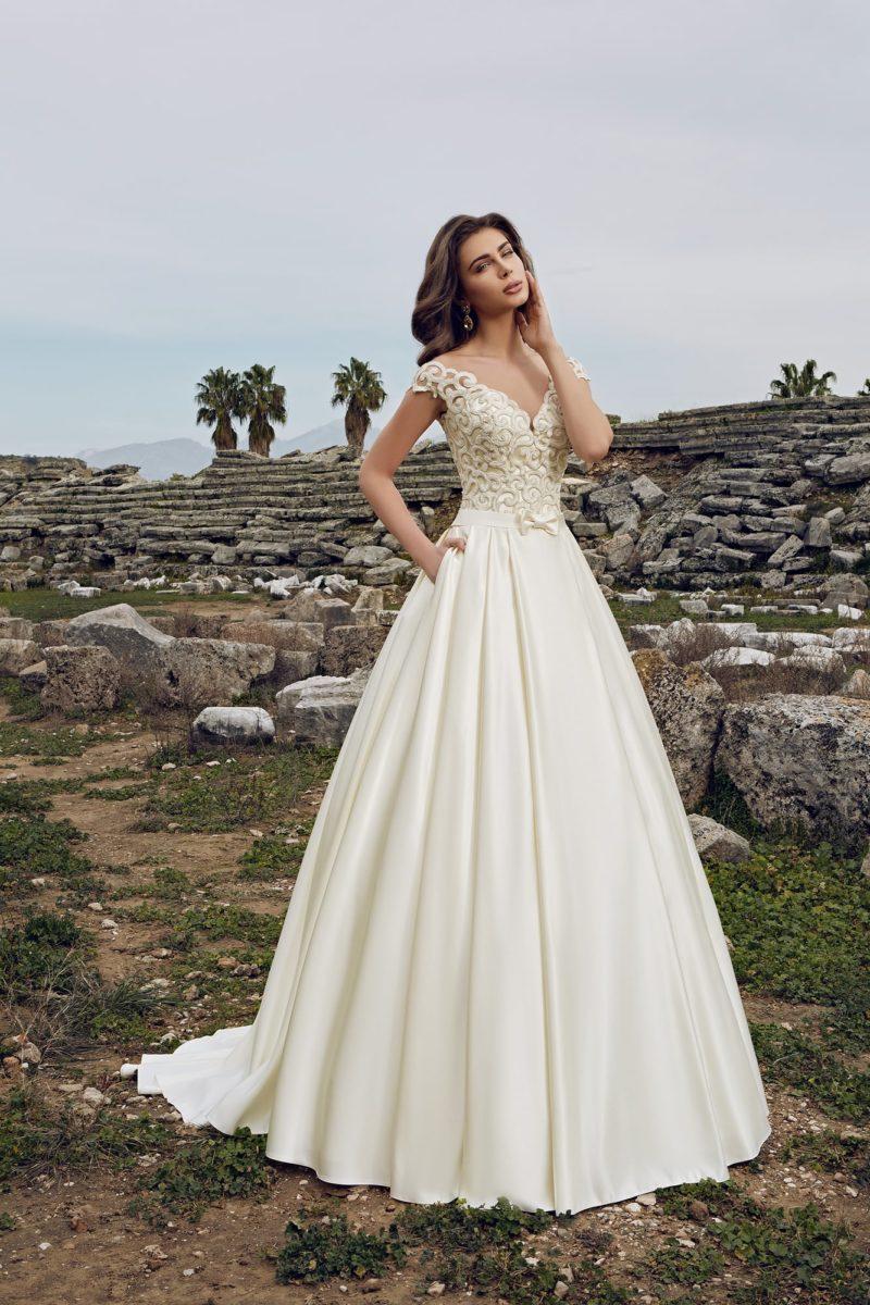 Атласное свадебное платье с изящными складками по юбке и кружевным декором лифа.