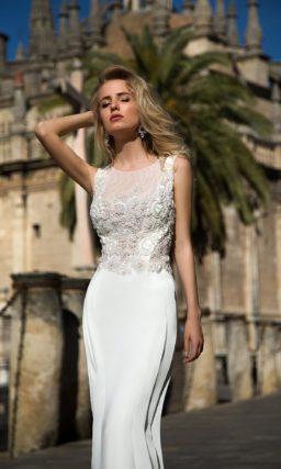 Закрытое свадебное платье прямого кроя, с декольте, оформленным полупрозрачной тканью.