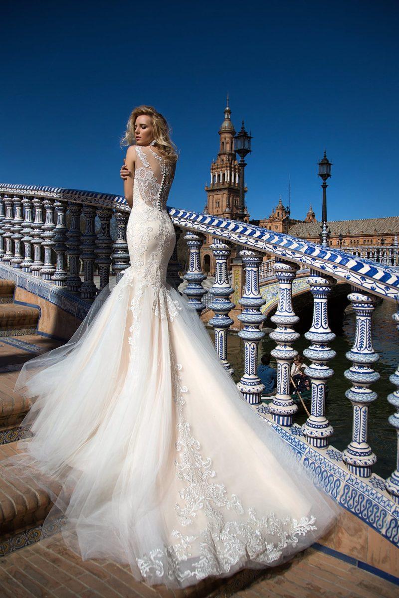 Свадебное платье цвета слоновой кости, с многослойной юбкой «рыбка» и кружевной спинкой.