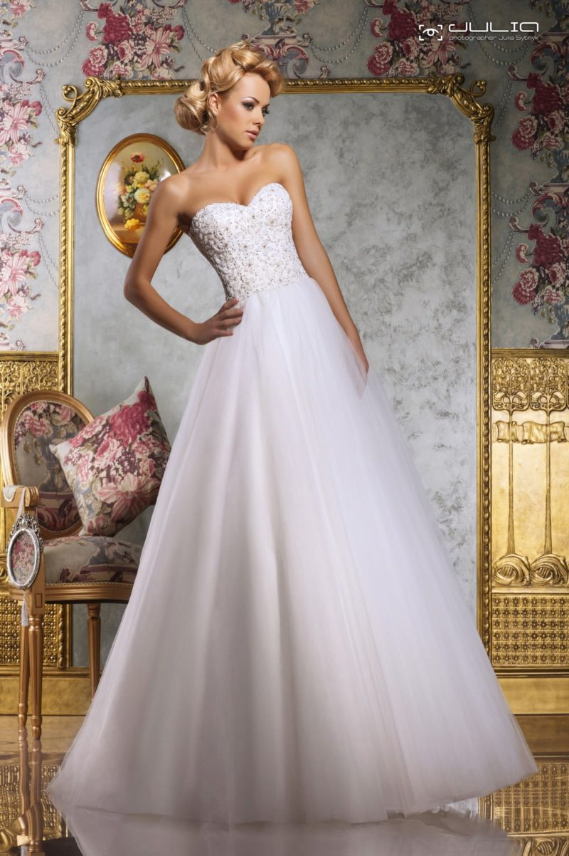 Пышное свадебное платье с открытым лифом, покрытым фактурным декором.