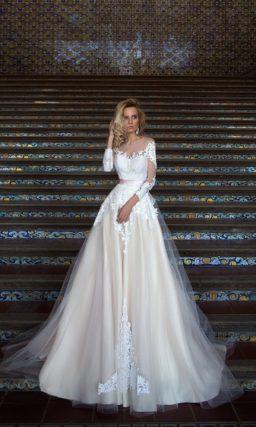 Пышное свадебное платье с полупрозрачной верхней юбкой и длинными кружевными рукавами.