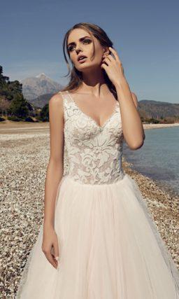 Свадебное платье цвета слоновой кости с V-образным декольте и кружевом по лифу.