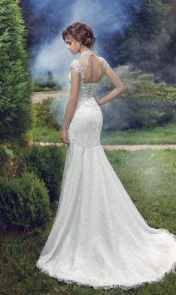 Облегающее свадебное платье, декорированное фактурное кружевной тканью, с воротником-стойкой.