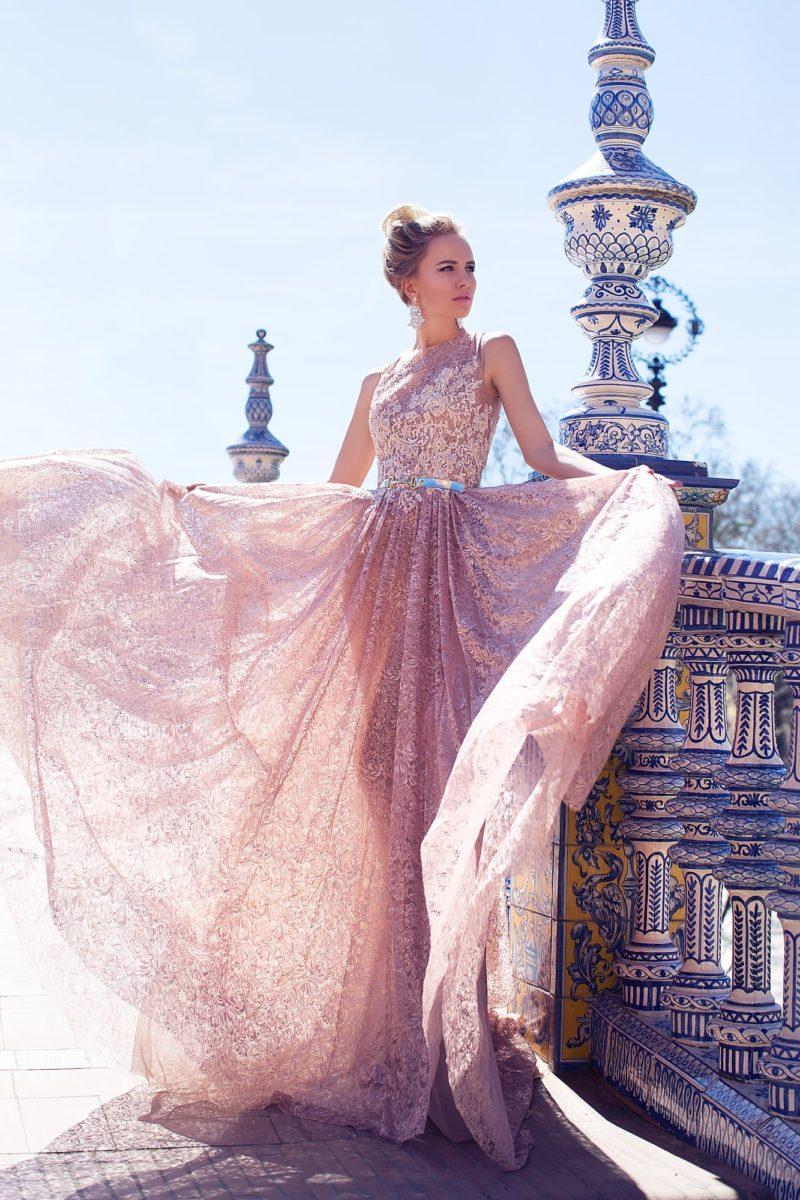 Роскошное свадебное платье розового цвета, по всей длине покрытое кружевной тканью.