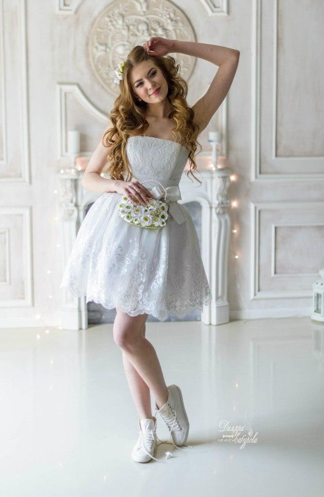 Кружевное свадебное платье с пышной юбкой длиной до середины бедра.