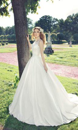 Пышное свадебное платье с узким поясом на талии и кружевным декором облегающего корсета.
