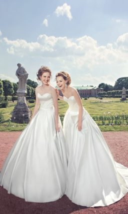 Сияющее свадебное платье из атласной ткани с открытым лифом-сердечком, украшенным драпировками.