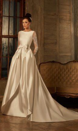 Атласное свадебное платье с закрытым лифом и оригинальной верхней юбкой со шлейфом.