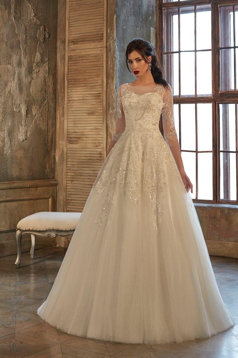 Скромное свадебное платье пышного кроя с рукавами длиной в три четверти и кружевом по верху.
