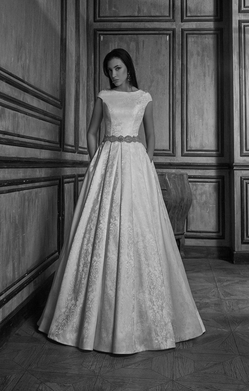Закрытое свадебное платье из фактурного атласа, дополненное широким поясом и скрытыми карманами.