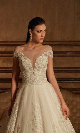 Пышное свадебное платье с притягательным портретным декольте, украшенным кружевом по краю.