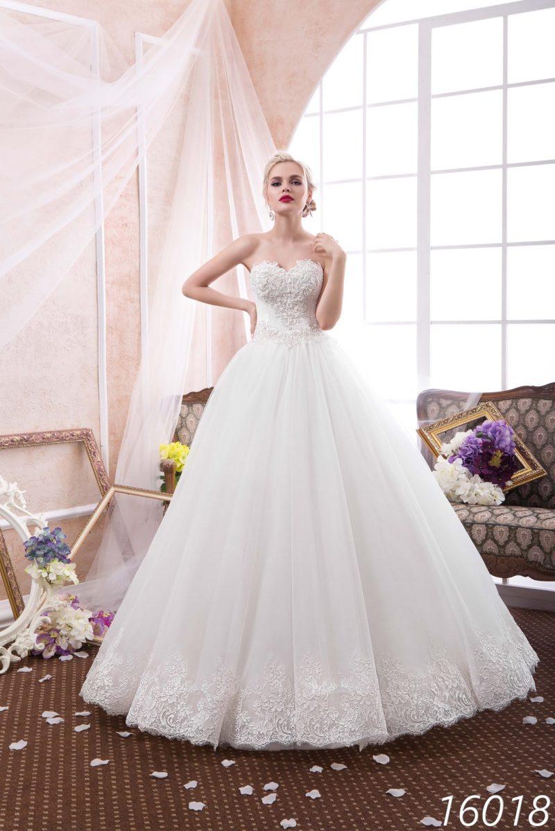 Классическое свадебное платье пышного кроя с открытым лифом, покрытым кружевной тканью.
