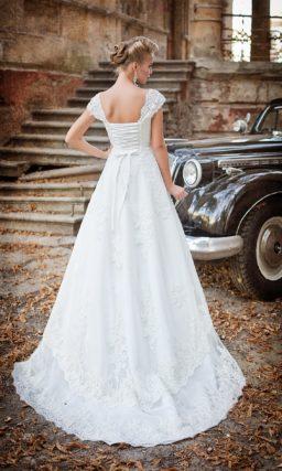 Свадебное платье с фактурным кружевным декором и элегантными бретелями на плечах.