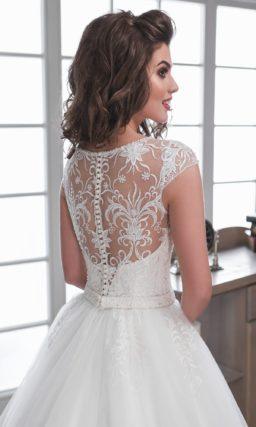 Нежное свадебное платье с многослойной юбкой и кружевной отделкой верха с коротким рукавом.