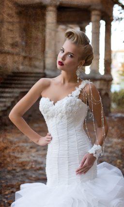 Свадебное платье с пышной юбкой, покрытой оборками, и асимметричным лифом.
