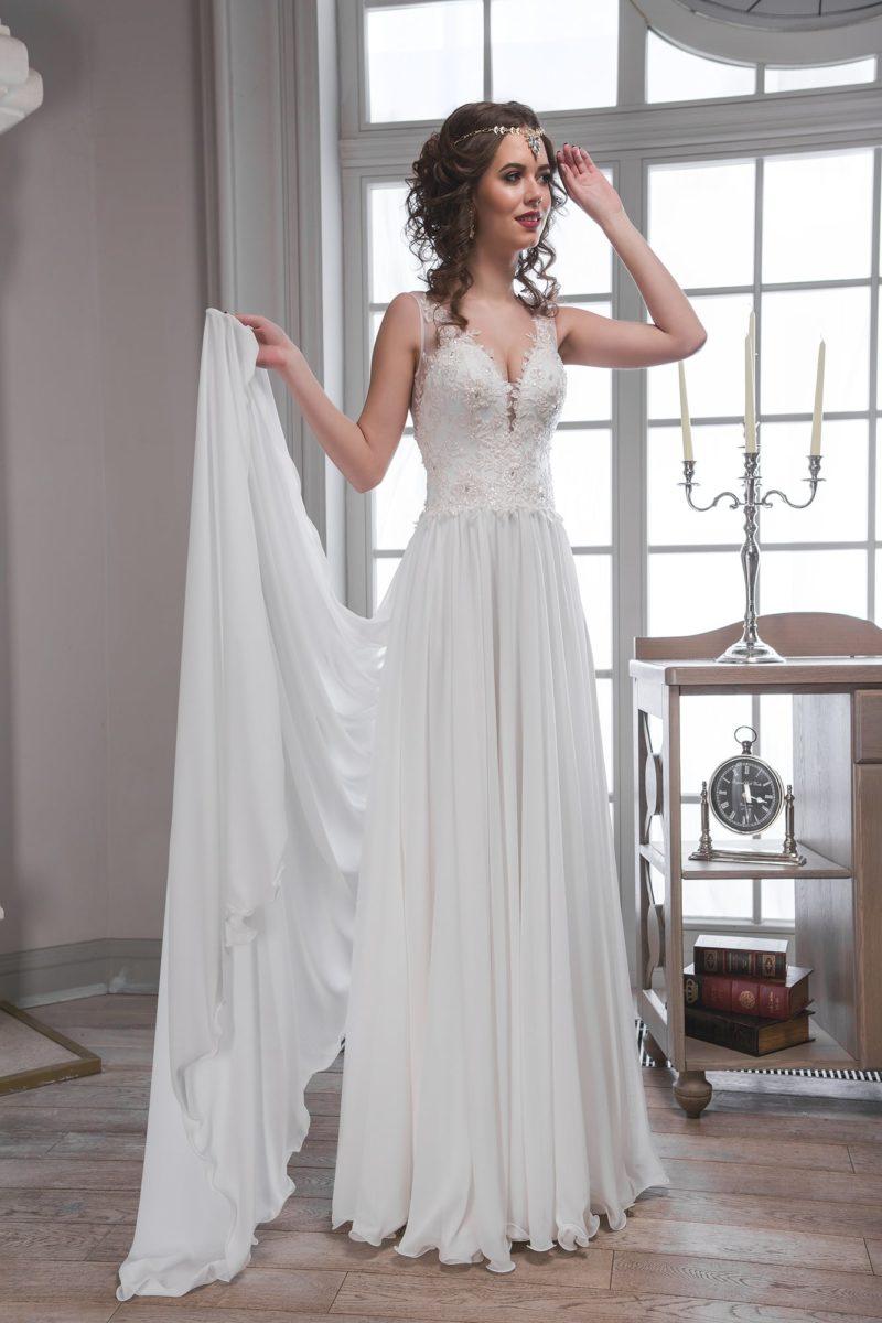 Прямое свадебное платье с глубоким декольте и объемной отделкой по облегающему корсету.