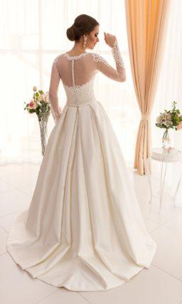Великолепное свадебное платье с пышной атласной юбкой и длинными кружевными рукавами.