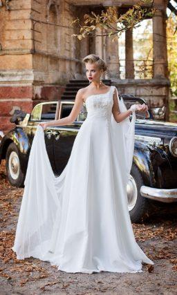 Свадебное платье с асимметричным лифом, украшенным бисером, и оригинальной накидкой.