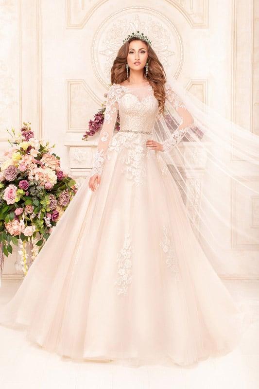 Пышное свадебное платье цвета слоновой кости с длинным кружевным рукавом и изящным поясом.