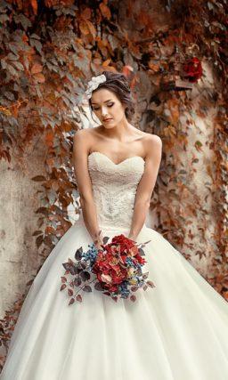 Элегантное свадебное платье с пышным низом и открытым корсетом, украшенным бисером.