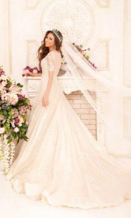 Изящное свадебное платье с кружевным декором верха, облегающим рукавом и бисерным поясом.