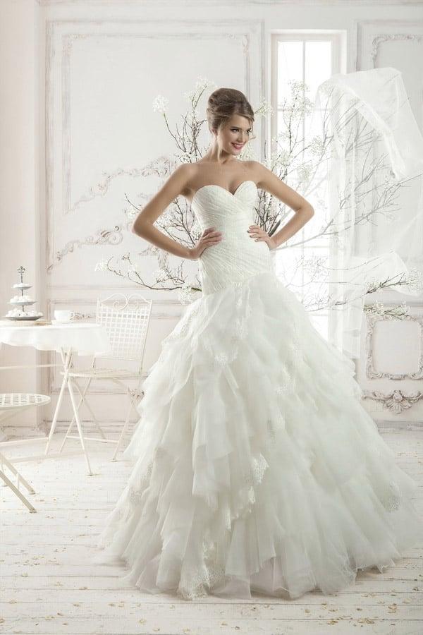 Стильное свадебное платье с открытым лифом и кокетливой юбкой из множества кружевных оборок.
