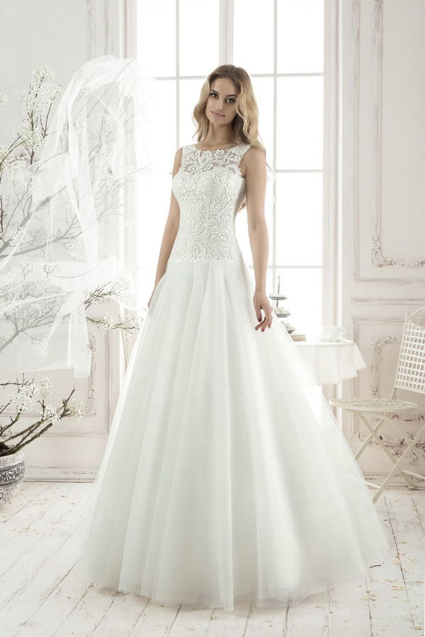 Сдержанное свадебное платье с многослойной юбкой без декора и кружевным закрытым верхом.