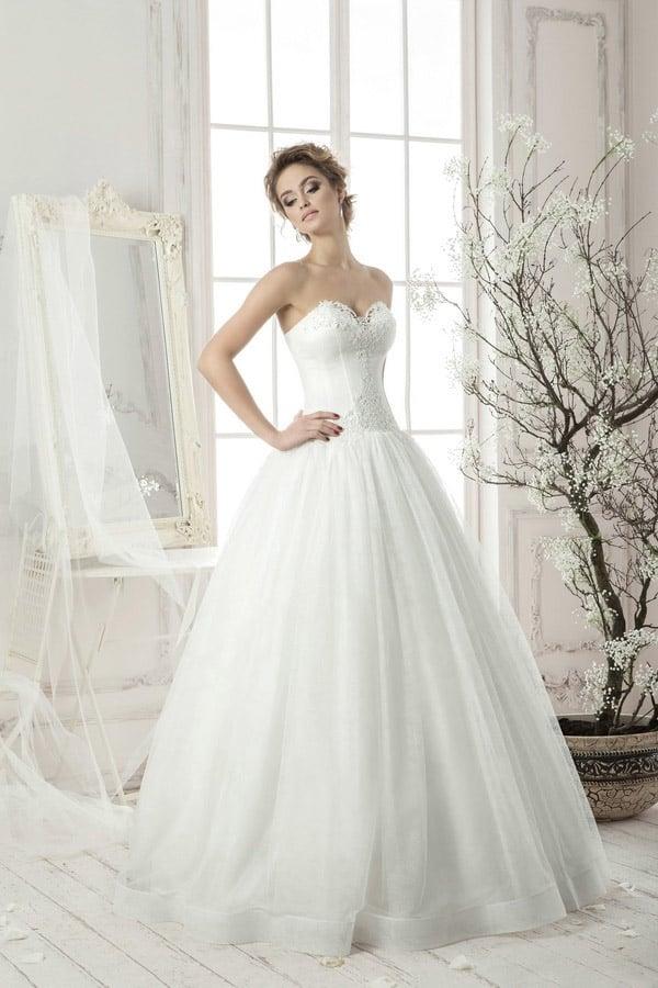 Изысканное свадебное платье с деликатным открытым корсетом и воздушной юбкой с отделкой подола.