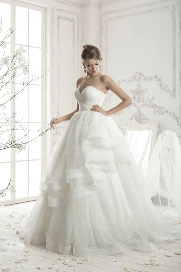 Роскошное свадебное платье с глубоким декольте в форме сердечка и многоярусной объемной юбкой.