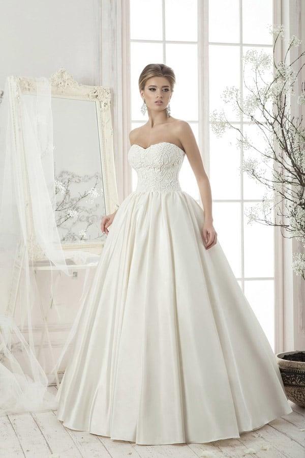 Глянцевое свадебное платье со складками по подолу и открытым кружевным корсетом.
