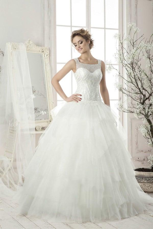 Закрытое свадебное платье с расшитым бисером верхом и пышной многослойной юбкой.