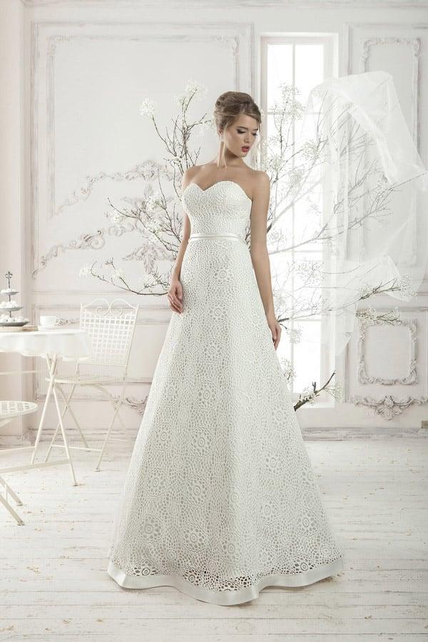 Открытое свадебное платье, покрытое ажурной тканью по всей длине и дополненное атласным поясом.