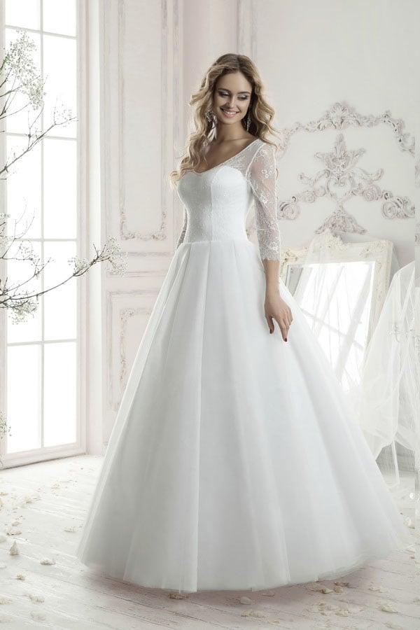 Женственное свадебное платье с округлым декольте и полупрозрачными кружевными рукавами.