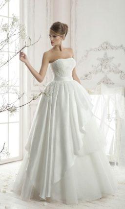 Необычное свадебное платье с фактурным верхом пышной юбки и изящным открытым корсетом.