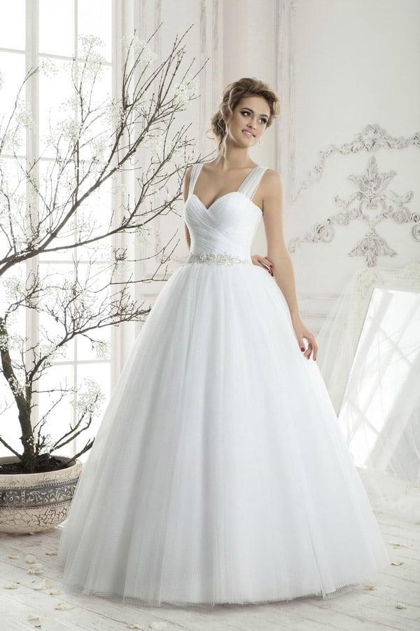 Свадебное платье с открытым лифом, дополненным полупрозрачными бретелями, и объемной юбкой.