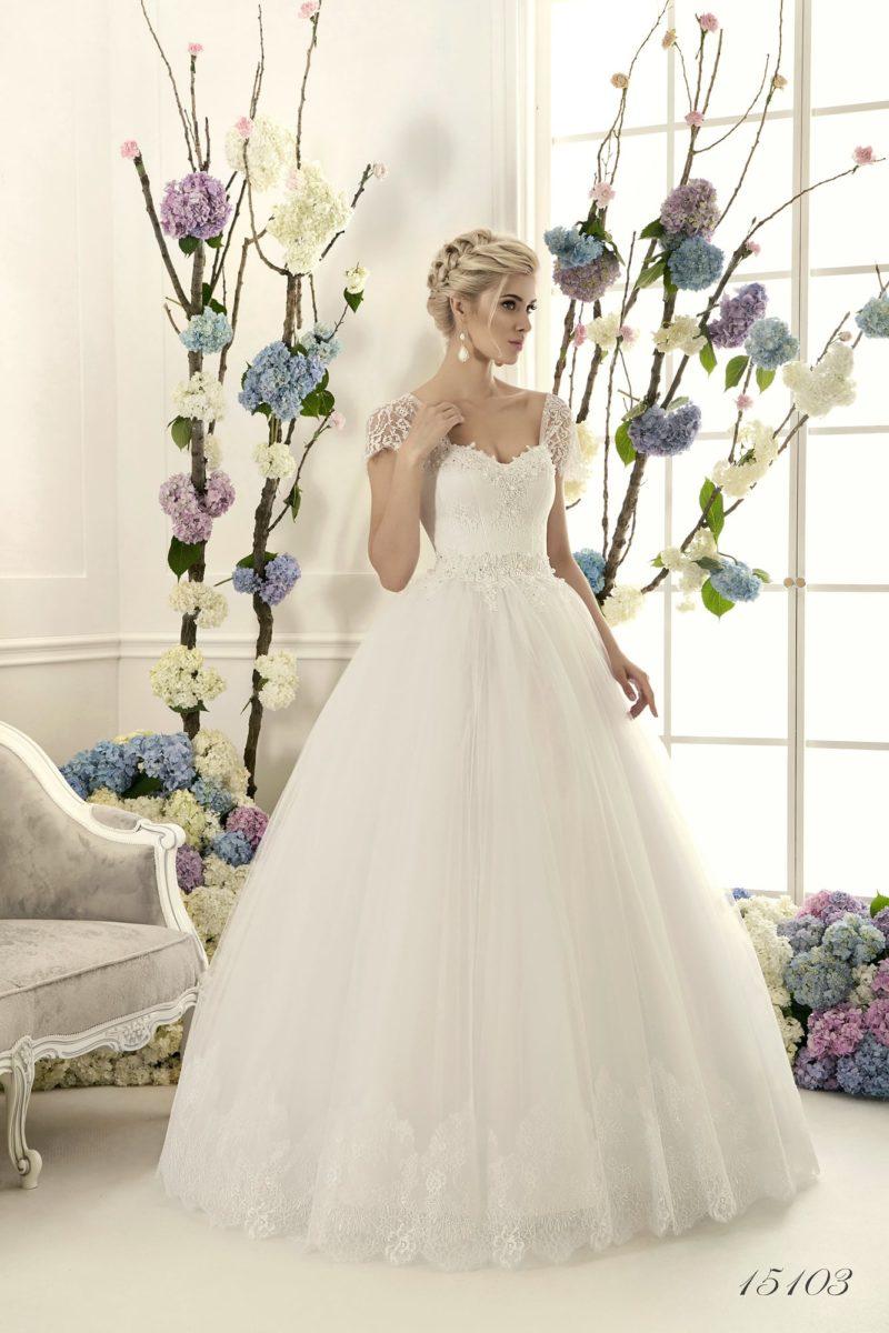 Пышное свадебное платье с короткими кружевными рукавами и многослойным подолом.