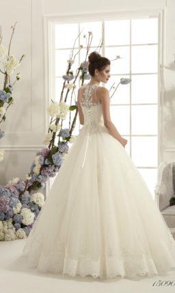 Роскошное свадебное платье с кружевным корсетом и многослойной юбкой с аппликациями.