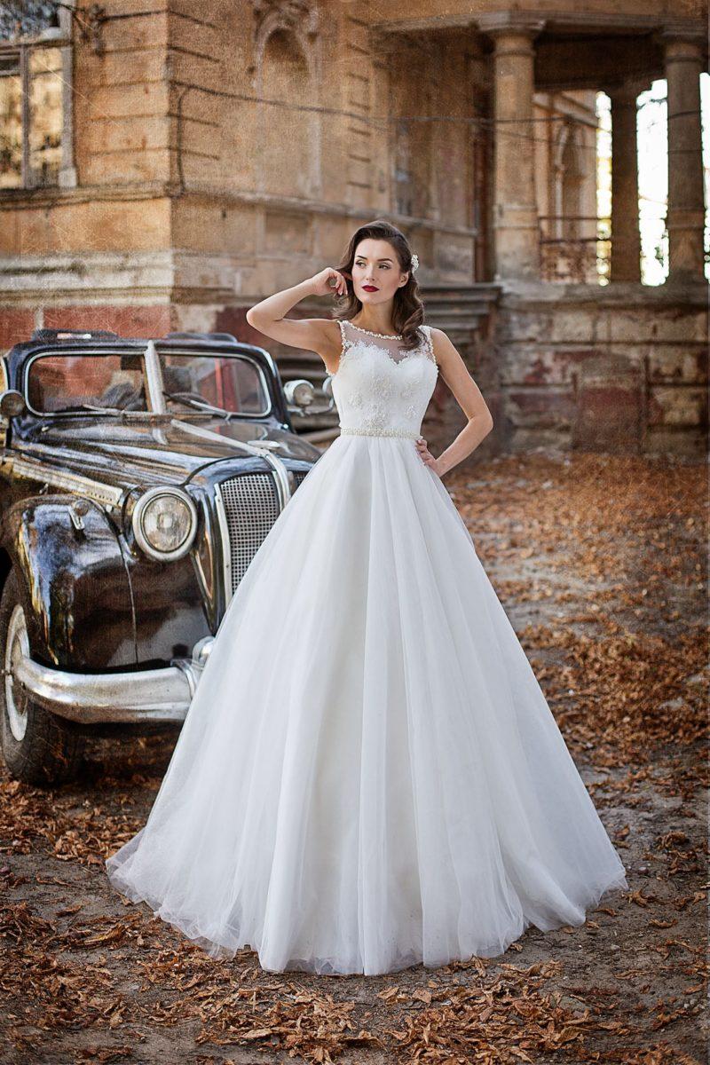 Изысканное свадебное платье с закрытым лифом и пышной юбкой, покрытой складками.