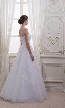 Классическое свадебное платье с многоуровневой юбкой и декорированным кружевом лифе.