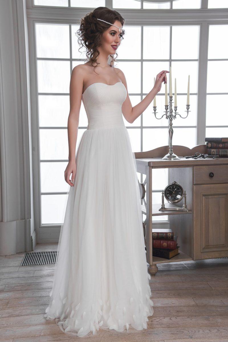 Деликатное свадебное платье с открытым декольте и объемной отделкой низа подола.