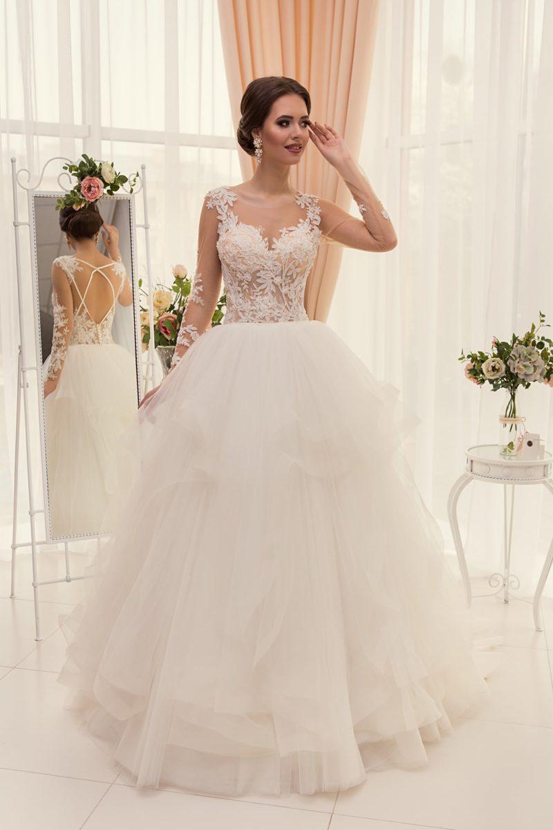 Пышное свадебное платье с роскошной юбкой и полупрозрачным корсетом, покрытым кружевом.