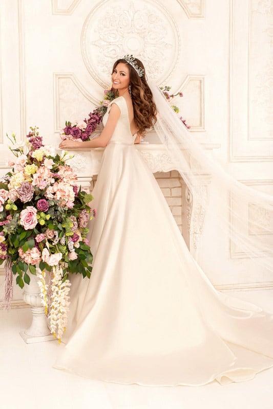 Сияющее свадебное платье из атласной ткани, с вырезом лодочкой и пышной юбкой со шлейфом.