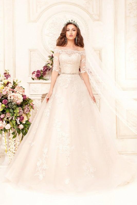 Романтичное свадебное платье с облегающими рукавами и аппликациями по пышной юбке.