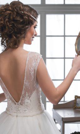 Пышное свадебное платье с элегантным закрытым верхом, оформленным тонкой тканью.