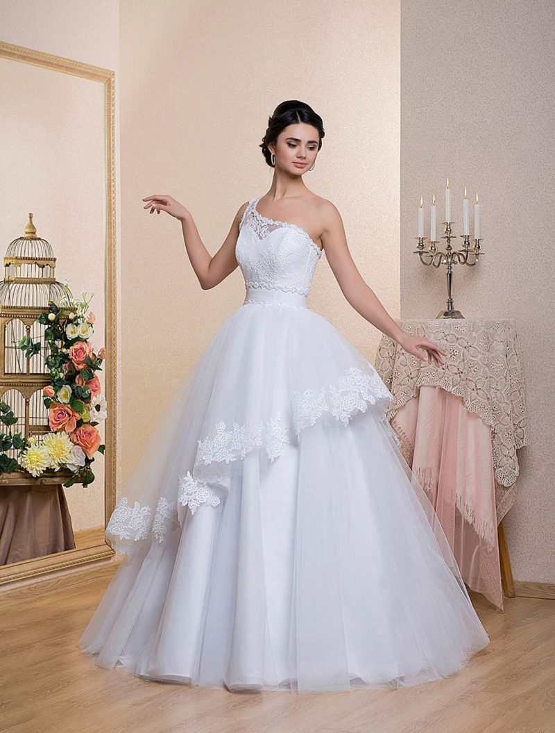 Пышное свадебное платье с полупрозрачным верхним слоем и асимметричным лифом.