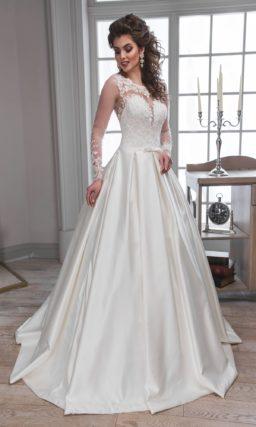 Очаровательное свадебное платье с пышной юбкой из атласа и длинным полупрозрачным рукавом.